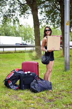 Hitch hiking woman stock photo, Young woman hitch hiking with a lot of luggage along a motorway all by herself by Corepics VOF