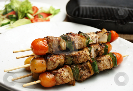 Kebabs stock photo, Freshly grilled Shish Kebabs. Grill pan and salad in the background. Shallow depth of field high key shot by Martin Darley