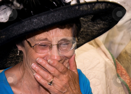 Elderly Woman Laughing stock photo, This elderly woman is laughing while wearing a black vintage hat and has her mouth covered with her hand. by Valerie Garner