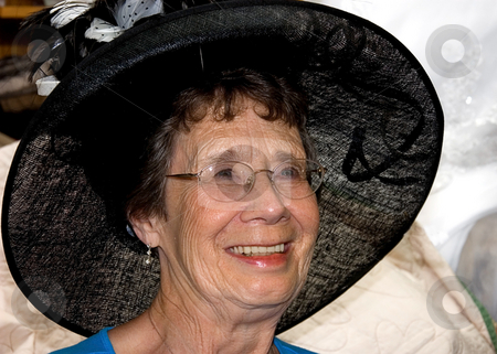 Senior Woman Smiling with Black Hat stock photo, This lovely senior citizen aged woman is wearing a black feathered vintage hat and is happy with a genuine smile. by Valerie Garner