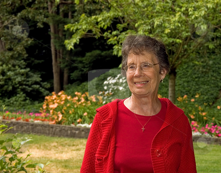 Older Woman Smiling In Garden Setting stock photo, This older woman in her seventies is smiling while in a garden setting and wearing red for a beautiful photo. by Valerie Garner