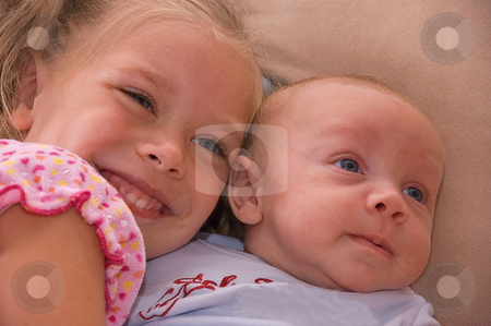 Baby Brother and Sister Together stock photo, This baby brother and 4 year old sister are sharing a moment together cuddling with affection and love. by Valerie Garner