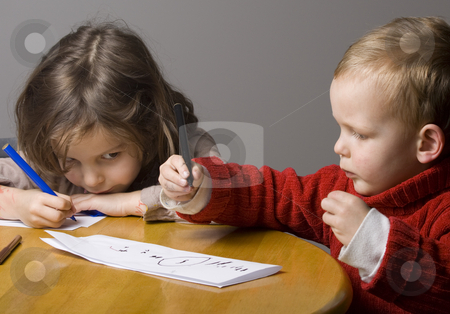 Boy and girl drawing stock photo, Little Boy and girl drawing by Jandrie Lombard
