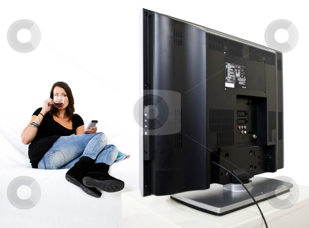 Woman watching TV stock photo, Young woman sitting comfortable on a white couch drinking a cup of tea with a remote control in her hands watching a huge flat screen television by Corepics VOF