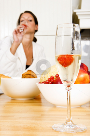 Champagne glass with strawberry stock photo, Champagne flute with a strawberry in it and a pretty brunette woman faintly in the background, representing a champagne breakfast on valentine's day by Corepics VOF