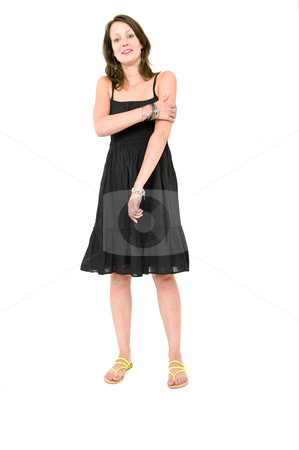 Woman - holding her arm stock photo, Full body portrait of a young brunette woman in a black summer dress, holding her arm being self aware by Corepics VOF