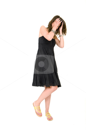 Woman - self aware stock photo, Full body portrait of a young brunette woman in a black summer dress, covering her head with her hands, laughing, and very much self-aware by Corepics VOF