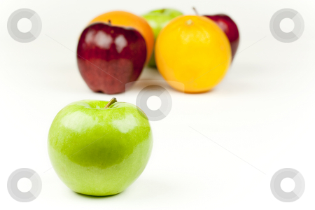 Apple and Friends stock photo, A green apple, with other fruits behind it by Patrick Noonan