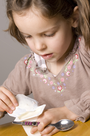 Girl eating yogurt stock photo, Little girl opening yogurt by Jandrie Lombard
