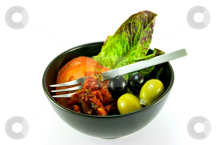 Salad Bowl and Fork stock photo, Black bowl with tomatoes, lettace and green and black olives and a small fork on a white background by Keith Wilson