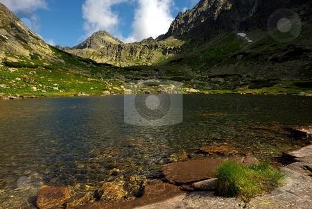 Mountain lake with a peak stock photo, Mountain lake with a peak in the background by Juraj Kovacik