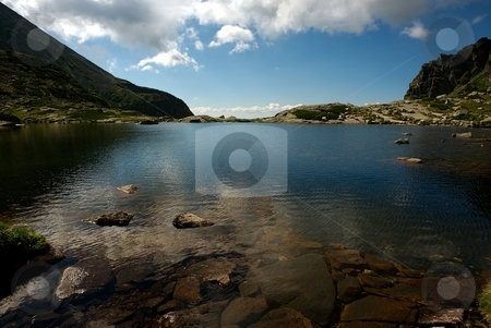 Mountain lake horizon stock photo, Mountain lake with straight horizon and reflecting blue sky with some clouds by Juraj Kovacik