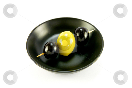 Three Olives in a Small Black Bowl stock photo, Two black and one green olive on a stick in a small black bowl on a white background by Keith Wilson