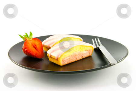 Strawberry Slices and Fork stock photo, Two pink strawberry sliced cakes with icing on the top with a half strawberry and small fork on a black plate with a white background by Keith Wilson