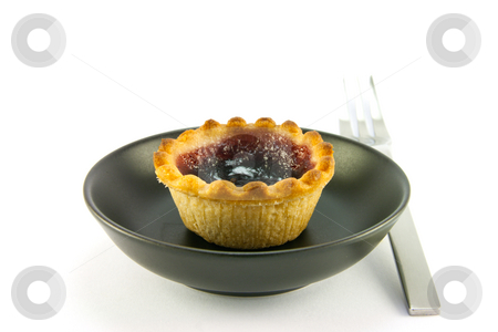 Strawberry Jam Tart stock photo, Single small red strawberry jam tart in a small black dish with a fork on a white background by Keith Wilson