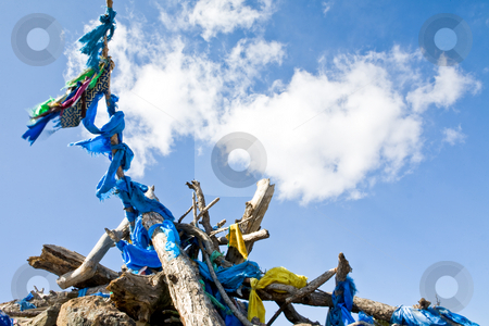 Pile of wood stock photo, A pile of wood with prayer flags on a sunny day by Mircea Struteanu