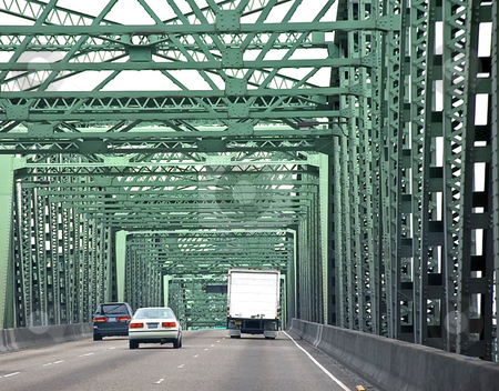 Vehicles Driving Across Bridge stock photo, This photo shows vehicles in two cars and one truck driving across a green metal bridge on a road. by Valerie Garner