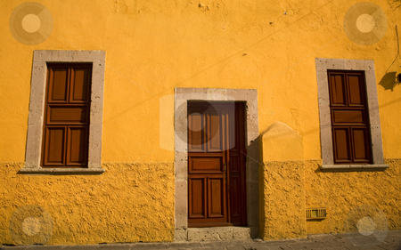 Yellow Adobe House Brown Doors Morelia Mexico stock photo, Bright Yellow Adobe House with brown doors Morelia Mexico by William Perry