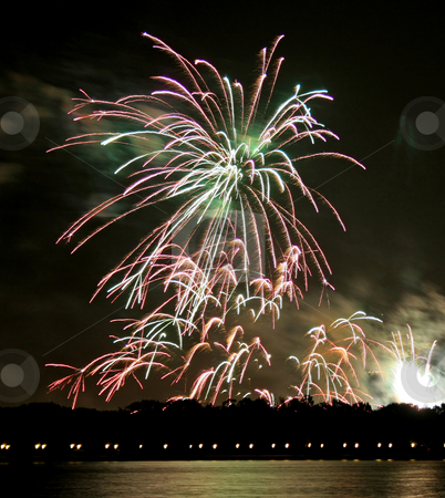 Fireworks stock photo, Fireworks in the dark sky over a lake. by Lucy Clark