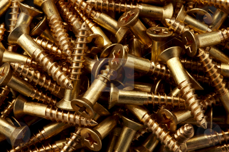 Close up shot of Wood Screws stock photo, Close up shot of dozens of gold colored phillips head wood screws by James Barber