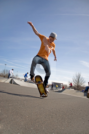 Skateboarding Tricks stock photo, A young skateboarder doing a stunt in a skate park. by Todd Arena
