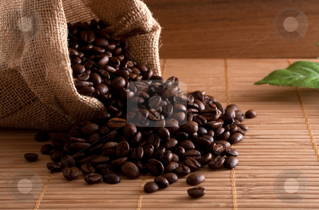 Coffee beans stock photo, A bunch of coffee beans, falling out of a sack on a wooden background by Alexander Zschach