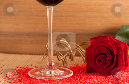 Red rose and wine glass stock photo, A red rose and a wine glass on a wooden bottom isolated on white background by Alexander Zschach