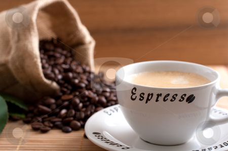 Coffee beans stock photo, A bunch of coffee beans, falling out of a sack and a cup of fresh coffee on a wooden background by Alexander Zschach
