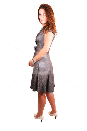 Pretty girl in gray dress. stock photo, Young lovely girl in a gray dress looking back over her shoulder, standing in the studio for white background. by Horst Petzold