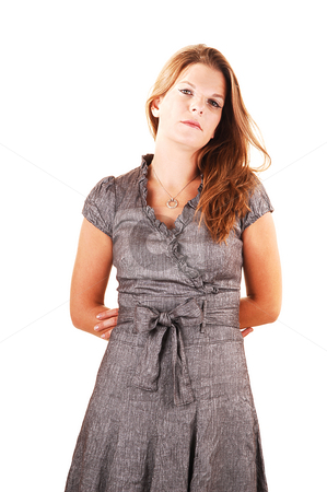 Pretty girl in gray dress. stock photo, Young lovely girl in a gray dress looking strait in the camera, crossing her  arms on the back, standing in the studio for white background. by Horst Petzold