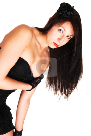 Young woman with long hair. stock photo, Young black haired woman in an black dress standing in the studio  for white background, has her right hand under her bust and leaning forward. by Horst Petzold