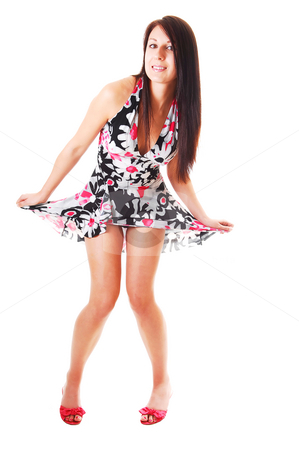 Woman lifting up her dress. stock photo, Lovely young woman in high heels standing in the studio with long brown