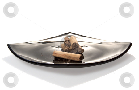 Cinnamon stock photo, Pieces of cinnamon on a black plate by Fabio Alcini