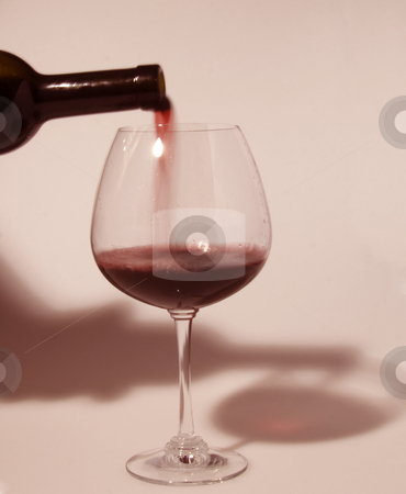 Wine stock photo, Bottle of red wine pouring in a glass by Fabio Alcini