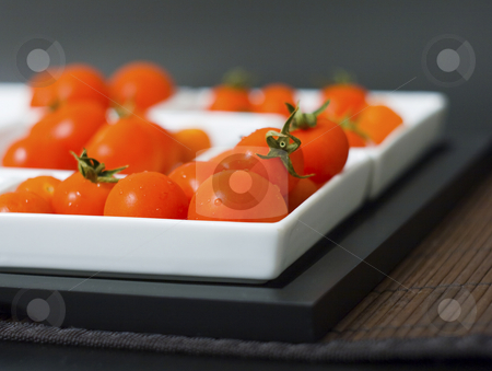Tomatoes stock photo, Some little tomatoes in white plates and wooden tablemats by Fabio Alcini