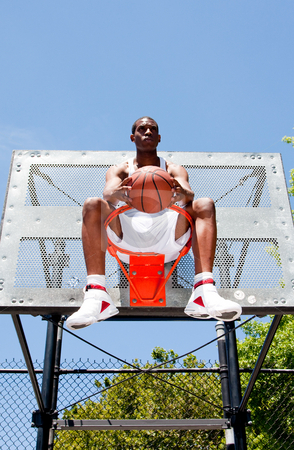 Basketball player sitting in hoop stock photo, Handsome sporty African-American male basketball player dressed in white and holding his ball outdoor on a summer day in a basketball court while sitting in the hoop. by Paul Hakimata
