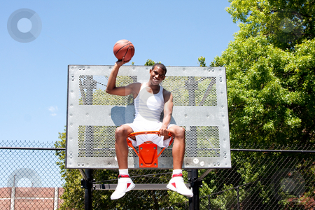 Champion basketball player sitting in hoop stock photo, Happy smiling handsome sporty African-American male basketball player dressed in white and holding his ball with one hand outdoor on a summer day in a basketball court while sitting in the hoop. by Paul Hakimata