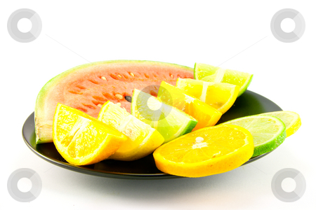 Watermelon with Citrus Wedges and Slices stock photo, Slice of juicy red watermelon with lemon, lime and orange wedges and slices on a black plate with a white background by Keith Wilson