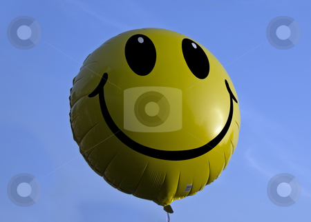 Yellow balloon stock photo, A yellow oker smiling balloon in the blue sky by Chris Willemsen