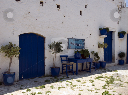 Blue greece stock photo, A chair and table in the typical blue color from greece for sitting outside, with flowers and a door by Chris Willemsen