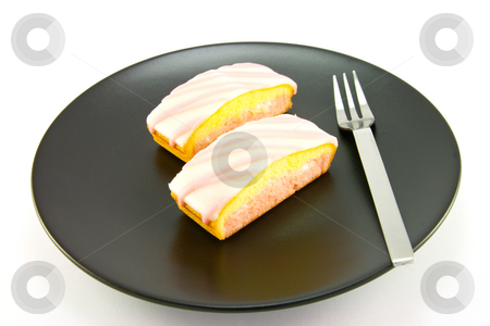 Strawberry Cake stock photo, Two pink strawberry sliced cakes with icing on the top with a small fork on a black plate with a white background by Keith Wilson