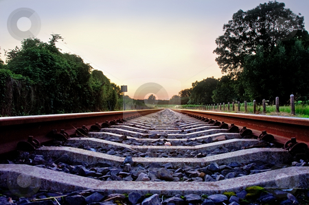 Railway tracks with pale pastel sunset stock photo, Railway tracks with pale pastel sunset and frog point of view by Karin Claus
