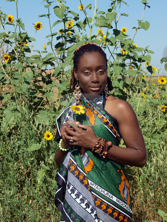 Young African American woman outdoors in native dress stock photo, Young black woman holding flower outdoors in green dress by Jeff Cleveland