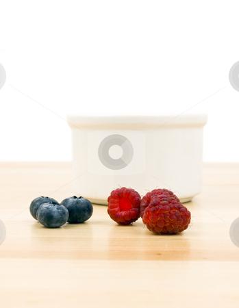 Raspberries and blueberries on table stock photo, Raspberries and blue berries on a wooden table by John Teeter