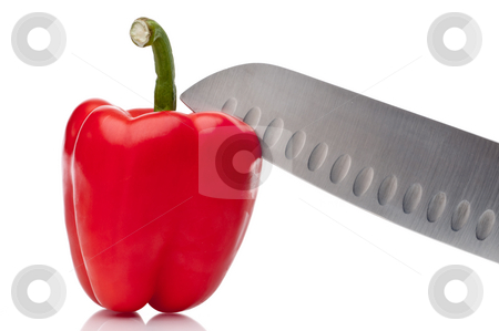 A horizontal image of a red pepper bei ng sliced on white stock photo, A horizontal image of a red pepper bei ng sliced on white by Vince Clements
