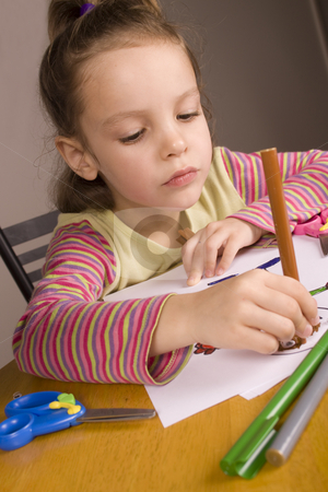 Girl Drawing stock photo, Little Girl Drawing a picture with a blue pair of scissors and some coloured pens by Jandrie Lombard