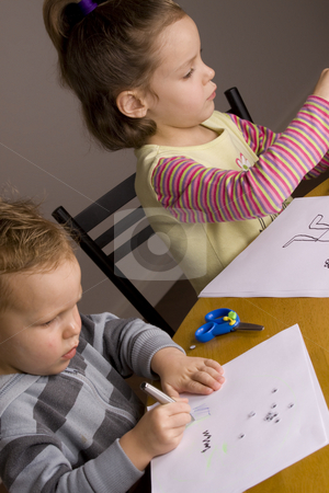 Boy and girl drawing stock photo, Girl and boy drawing a picture at the table by Jandrie Lombard
