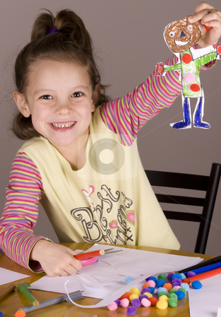 Girl showing her cutout drawing stock photo, Girl showing her picture that she just cut out by Jandrie Lombard