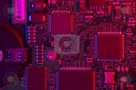 Electronic Technology stock photo, Closeup shot of a circuit board, microchips and other electronic components. Strong oblique red and blue lighting by Martin Darley