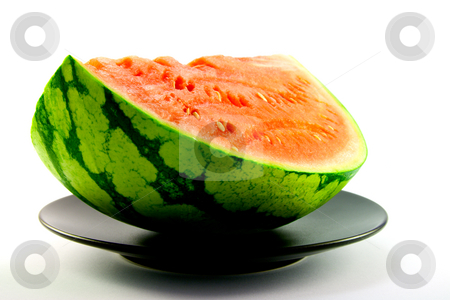 Watermelon on a Black Plate stock photo, Slice of watermelon with green skin and red melon with seeds on a black plate with a white background by Keith Wilson